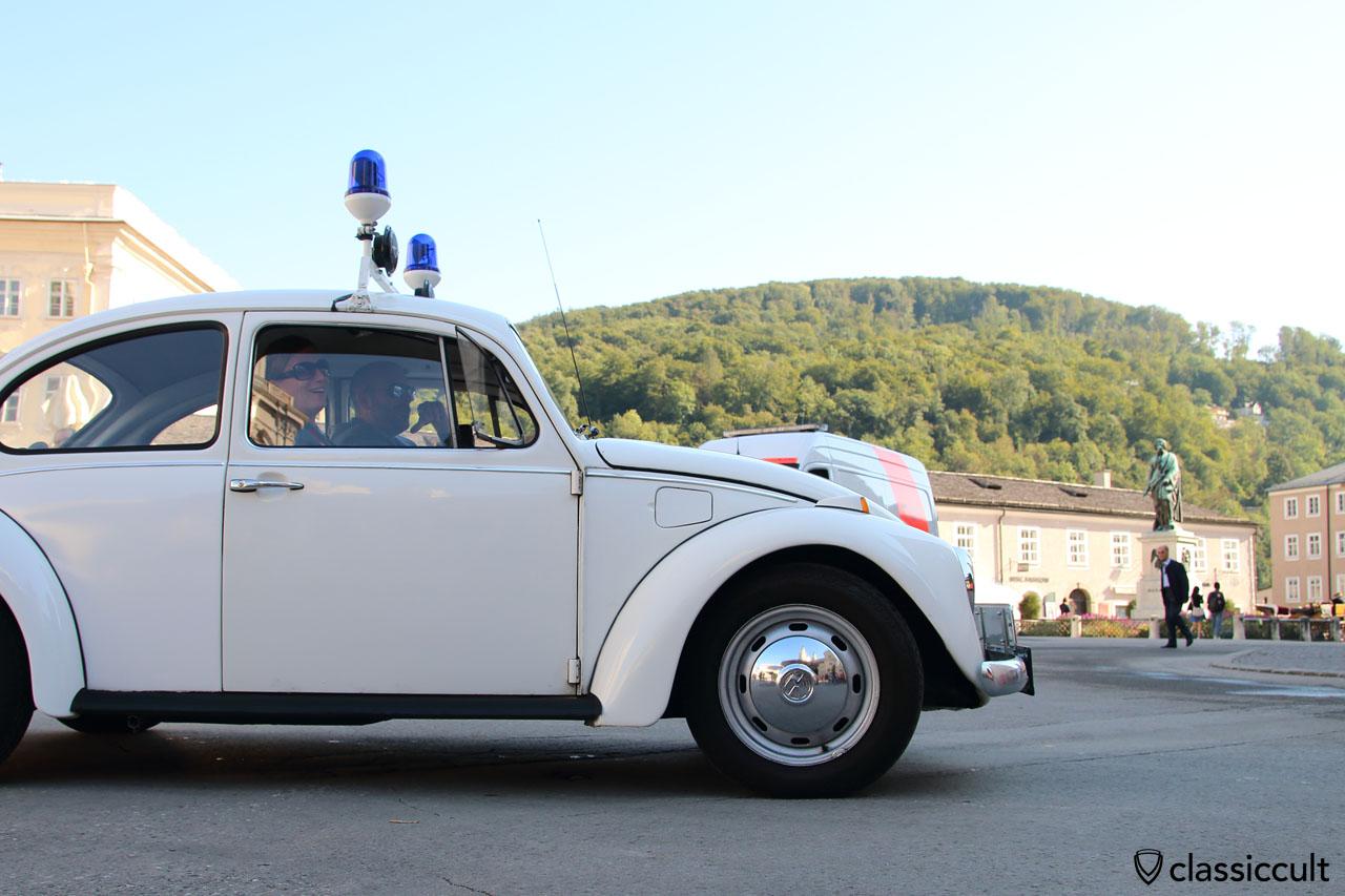 VW Käfer und stolze Besitzer vorbei am Mozart Denkmal in Salzburg