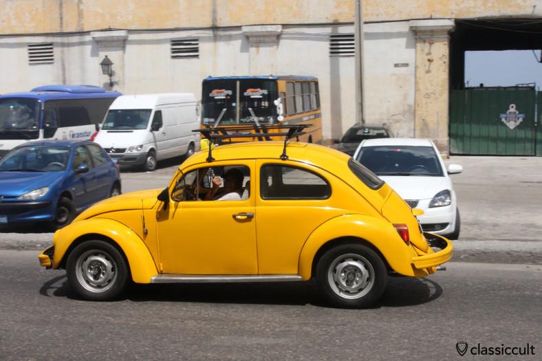 Classic VW Beetle driving near El Museo del Ron Havana Club, Cuba, March 28, 2014