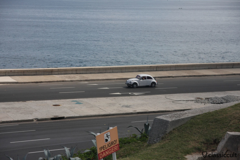 VW Beetle cruising at The Malecón roadway along the coast in Havana. Picture was taken from the terrace of Hotel Nacional de Cuba, March 29, 2014.