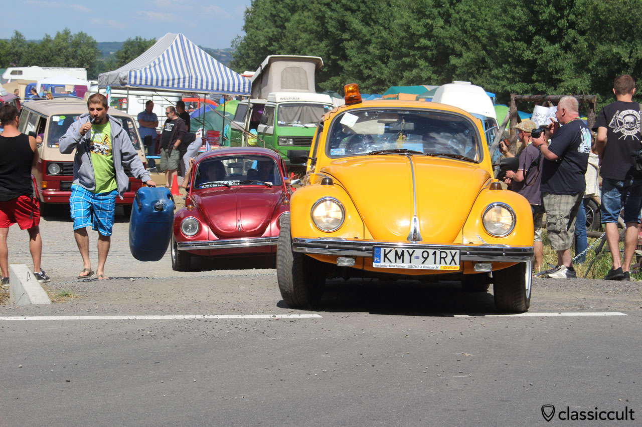 yellow VW Beetle with flashing lamp drives off to Wawel Castle