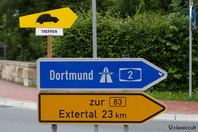 "VW Beetle road sign to ""Treffen"" to 6th International Vintage Volkswagen Show Hessisch Oldendorf 2013. Thank you. The show was easy to find and I had a smile in my face when I saw the first road sign like that. HO Team made different style ""Treffen"" signs, e.g. one has a VW Beetle with Caravan for Camping. Well done!"