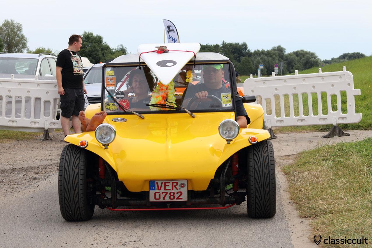 gelber VW Buggy mit Surfboard und Arne am Steuer