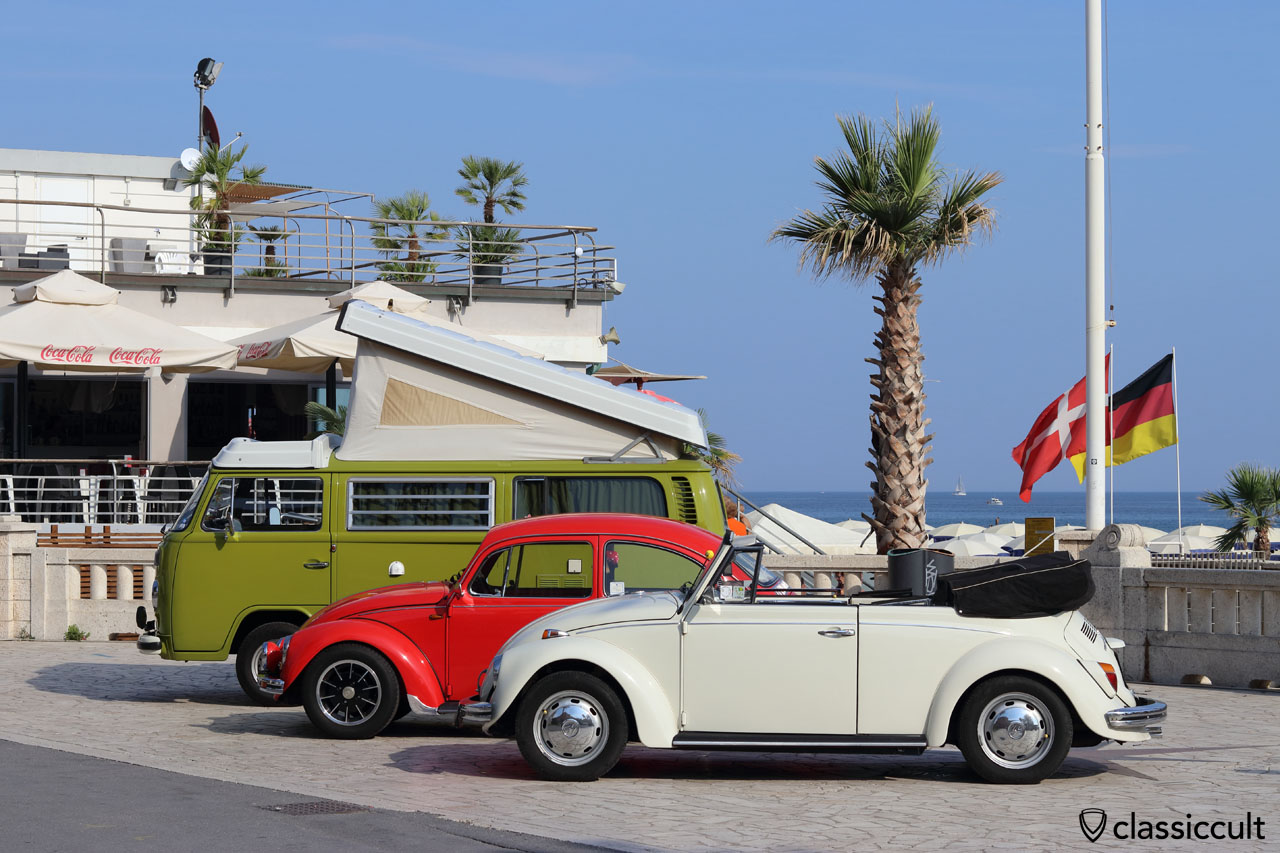 WOW, RiVWiera 2016, white VW Cabrio, red Maggiolino. green Westy Bus, Finale Ligure Beach, the flags in the background indicate that this beach is in German hands