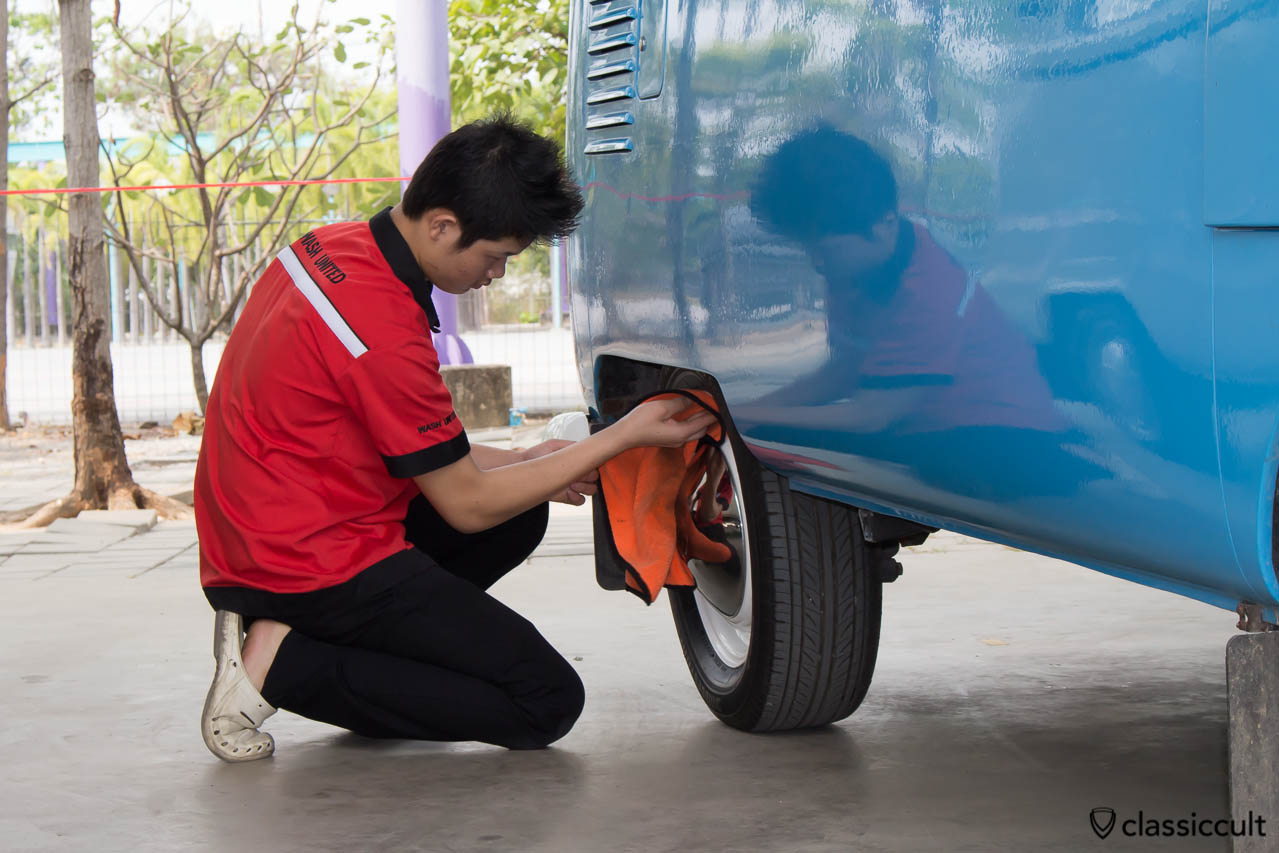 Boy polishing very well the Volkswagen of the King of Thailand.