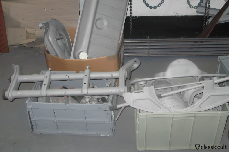 VW Beetle parts sandblasted. Front axle, tank and motor plates freshly sandblasted. All VW Beetle parts which are original black received epoxy primer and were painted black. All other parts, e.g. the body, fenders, doors and hubcaps received the first layer of filler after the epoxy primer.