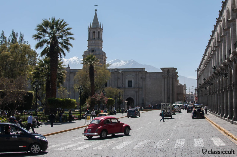 VW Bug with the Basilica Catedral of Arequipa and snow-capped mountains, Peru, May 8, 2013